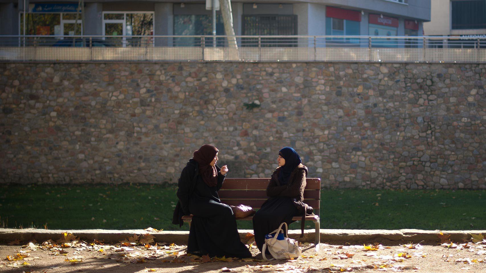 Dos mujeres con hiyab, sentadas en un banco.