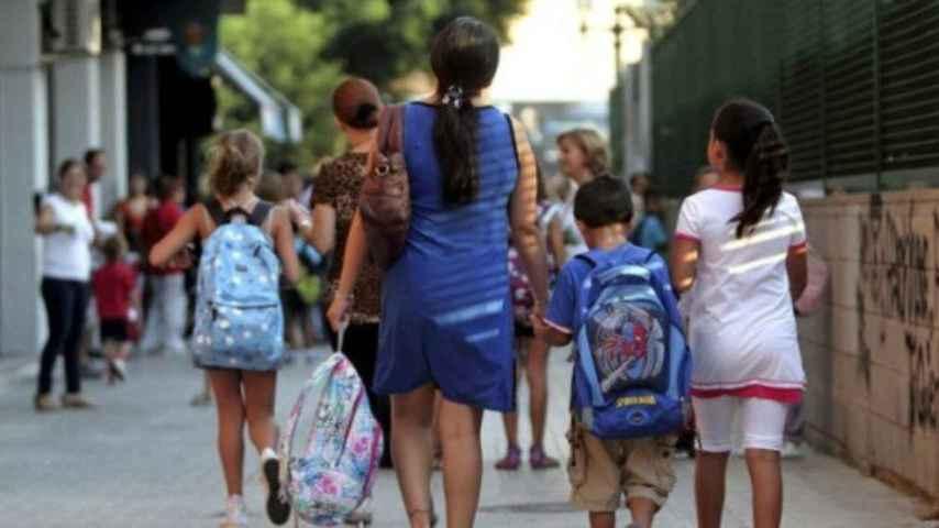 Madre acompaña a sus hijos al colegio