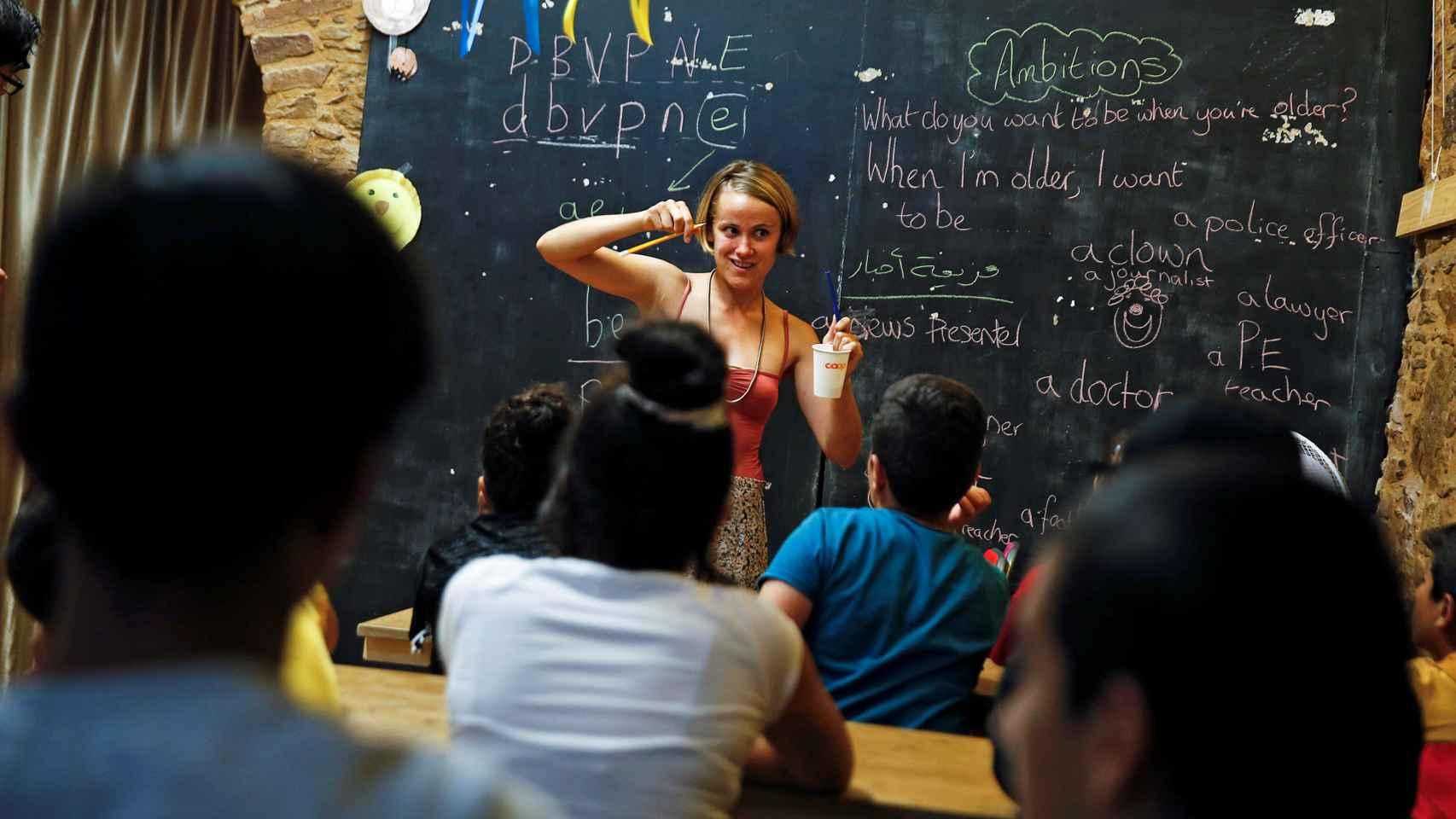 Voluntaria británica impartiendo clase a refugiados en Grecia.
