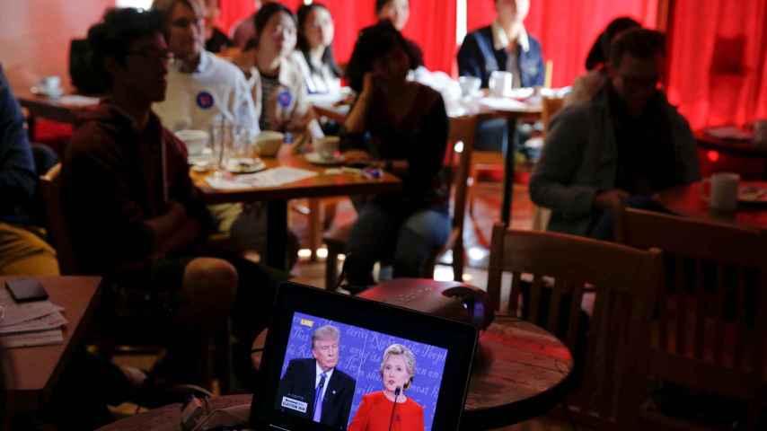 Un espectador, en un bar, sigue el debate de Clinton-Trump en un portátil.