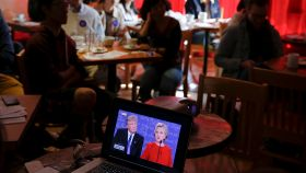Un espectador, en un bar, sigue el debate de Clinton-Trump en un ordenador.