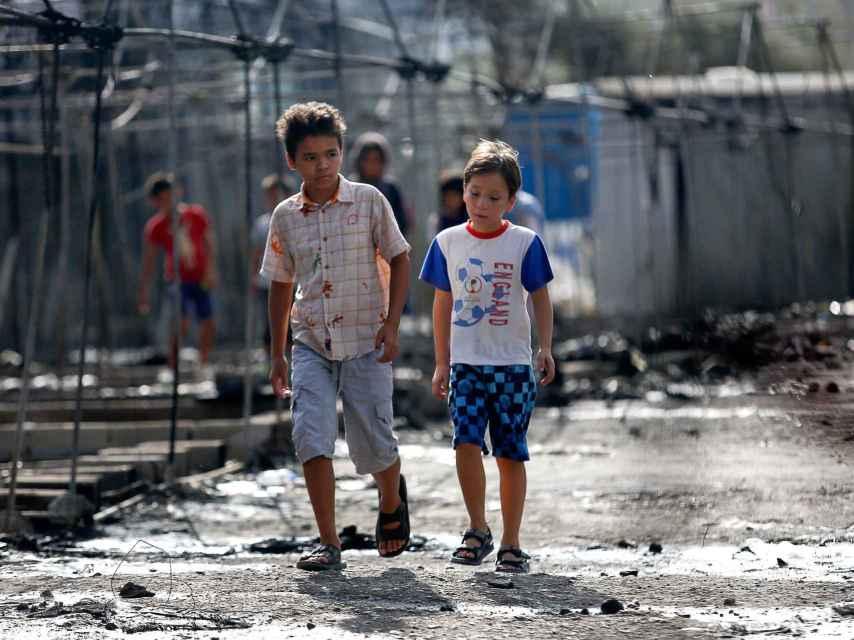 Unos niños caminan entre las cenizas de las casetas en el campo de Moria (Grecia) tras el fuego.
