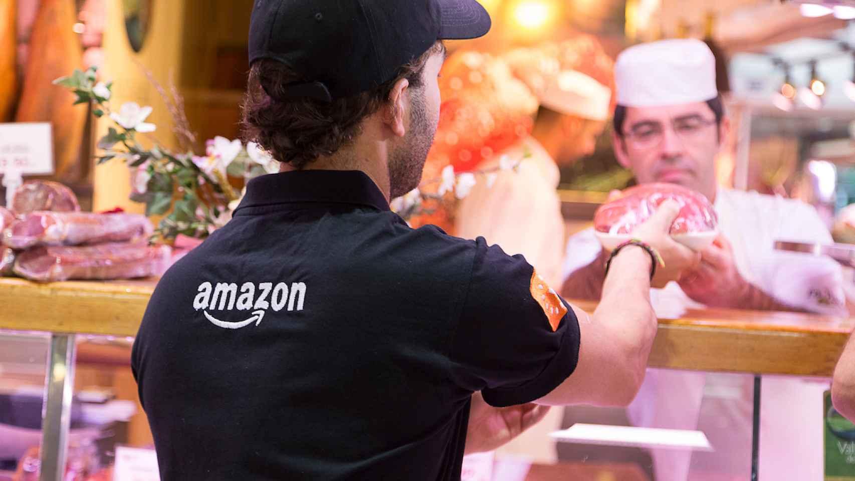 Un repartidor de Amazon recoge un producto en el Mercado de la Paz para su servicio 'Prime Now'.