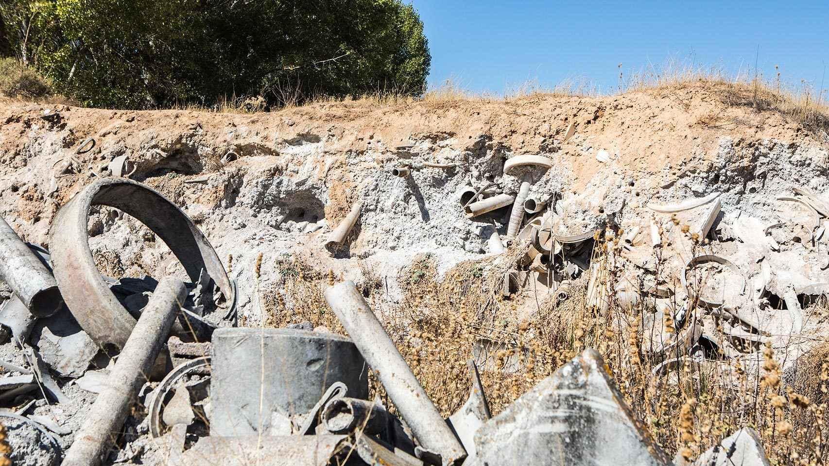 Restos de tubos y ladera degradada formada por el lodo.