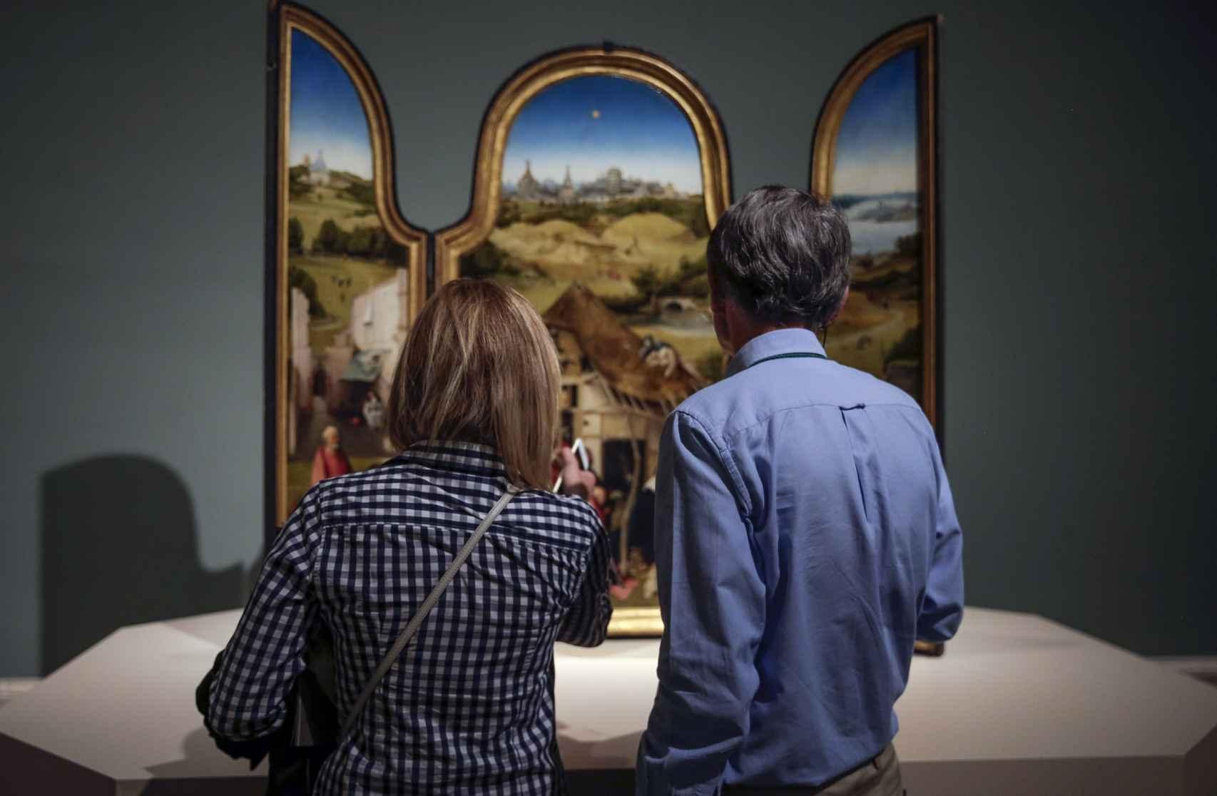 Dos visitantes ante el tríptico de La adoración de los magos.
