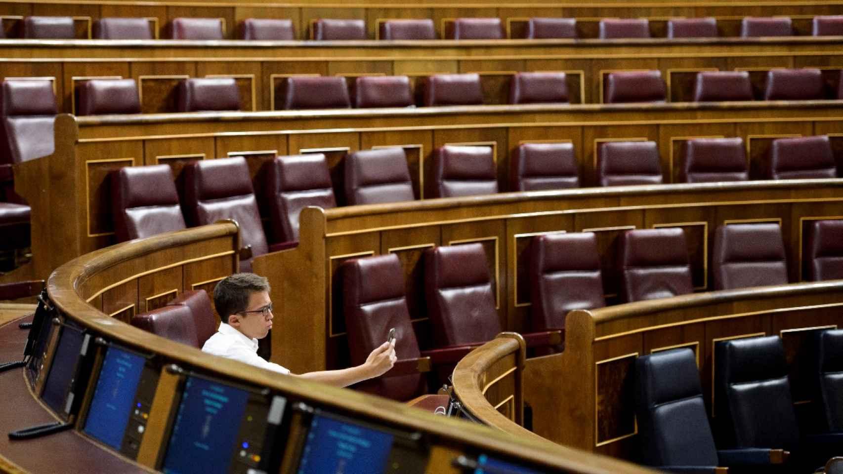 Íñigo Errejón posa para su móvil en su escaño del Congreso de los Diputados.