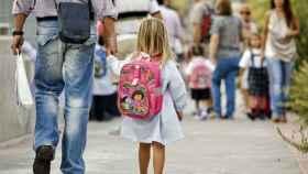 Una niña camina con su padre al colegio.