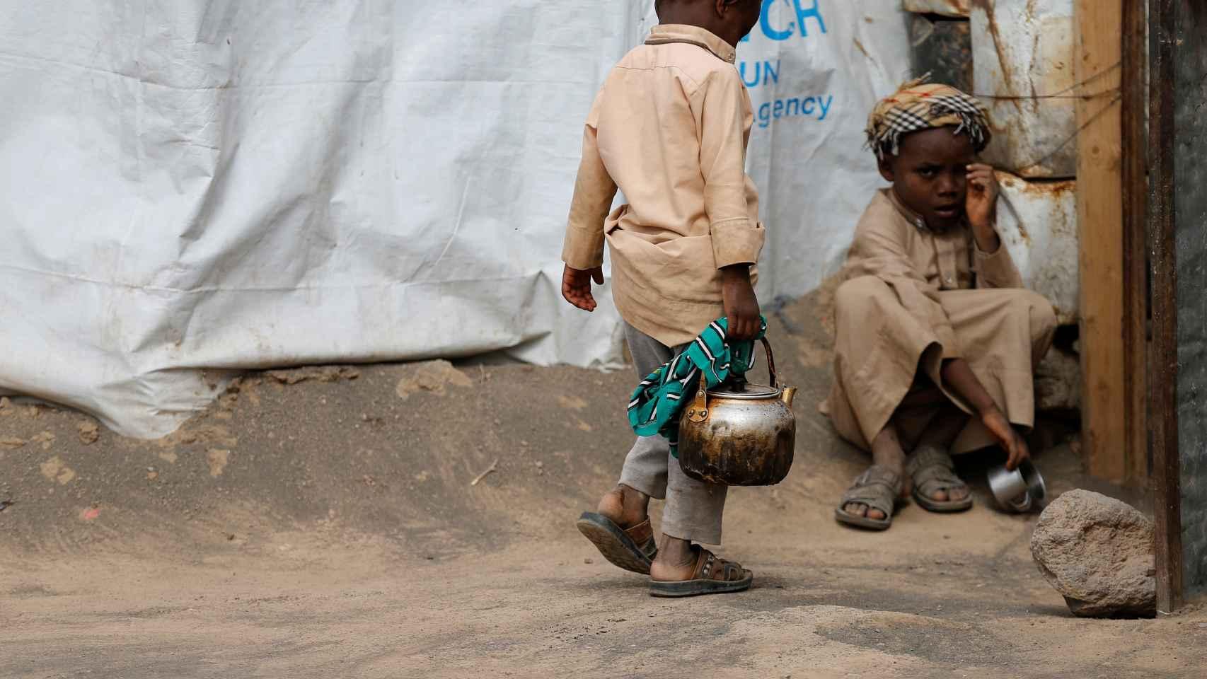 Un niño carga con una tetera en un campo de desplazados cerca de Sanáa. | Reuters