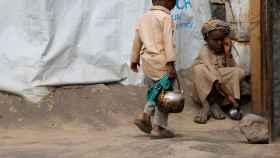 Un niño carga con una tetera en un campo de desplazados cerca de Sanáa.   Reuters