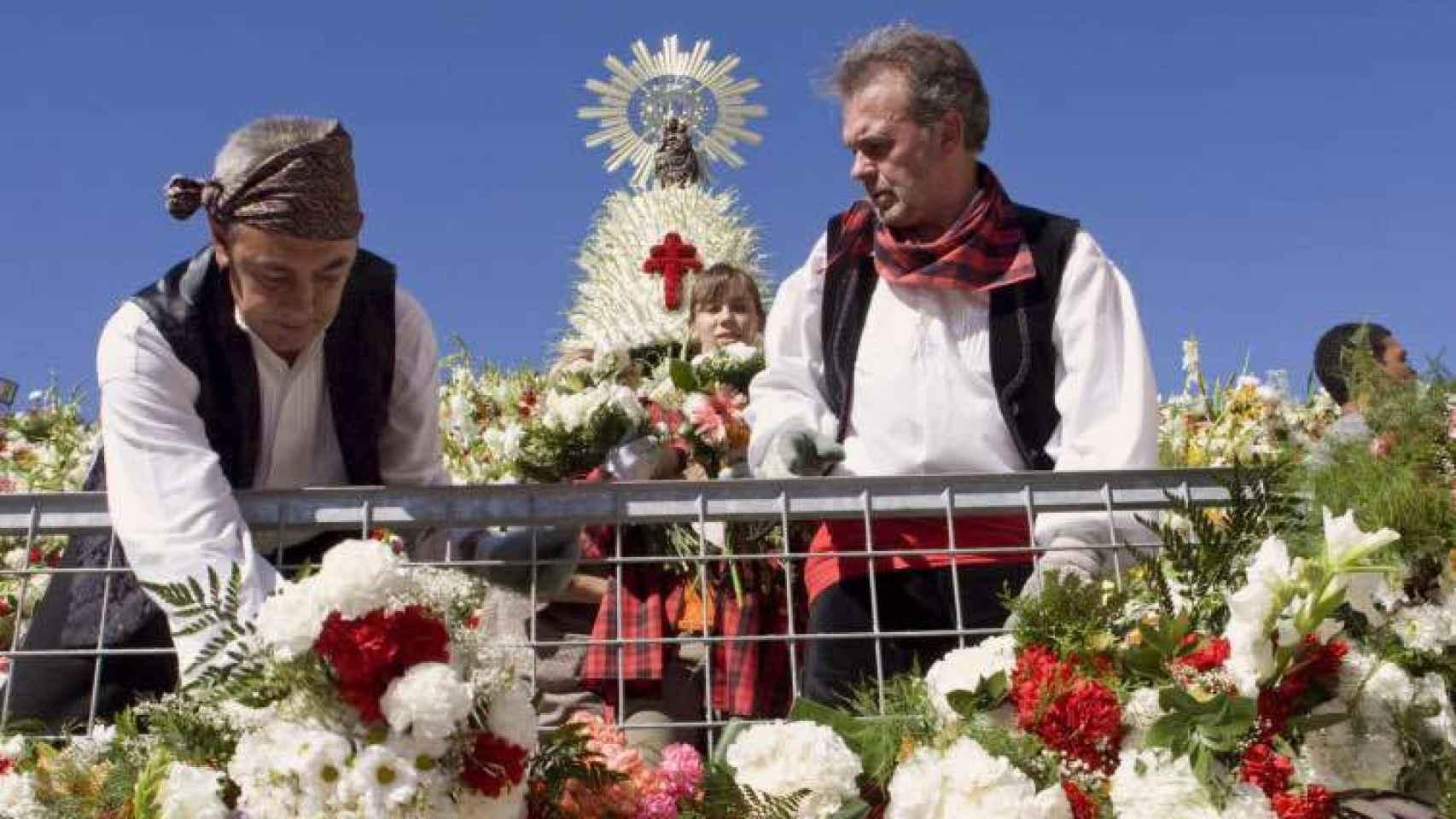 Voluntarios colocan flores en el manto de la Virgen