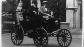 Dos hombres circulando en un vehículo americano de la década de 1890.