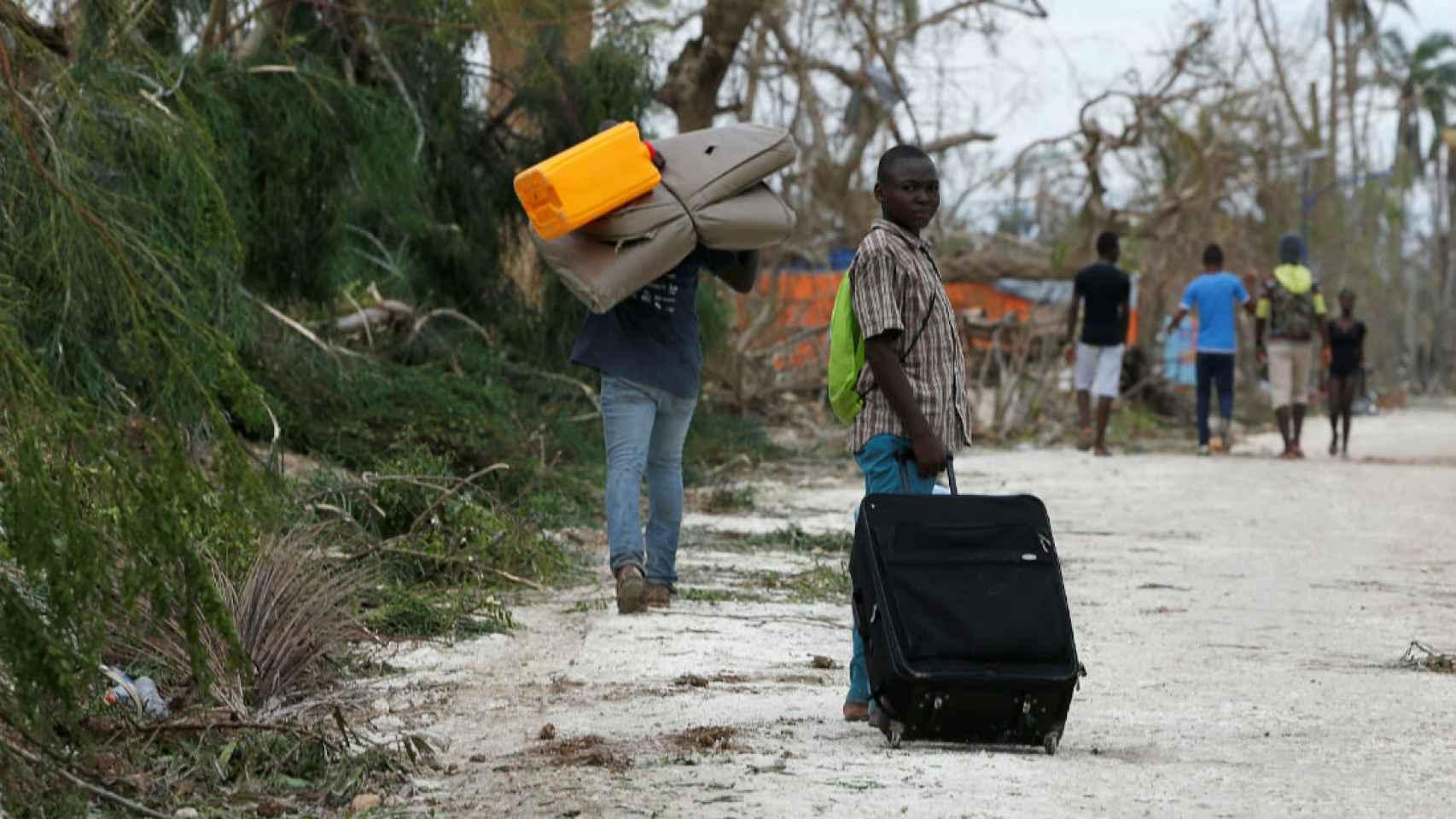 Personas recogiendo sus pertenencias después de que el huracán arrasara sus hogares en Haití.