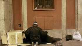 Un indigente se dispone a pasar la noche en un porche.
