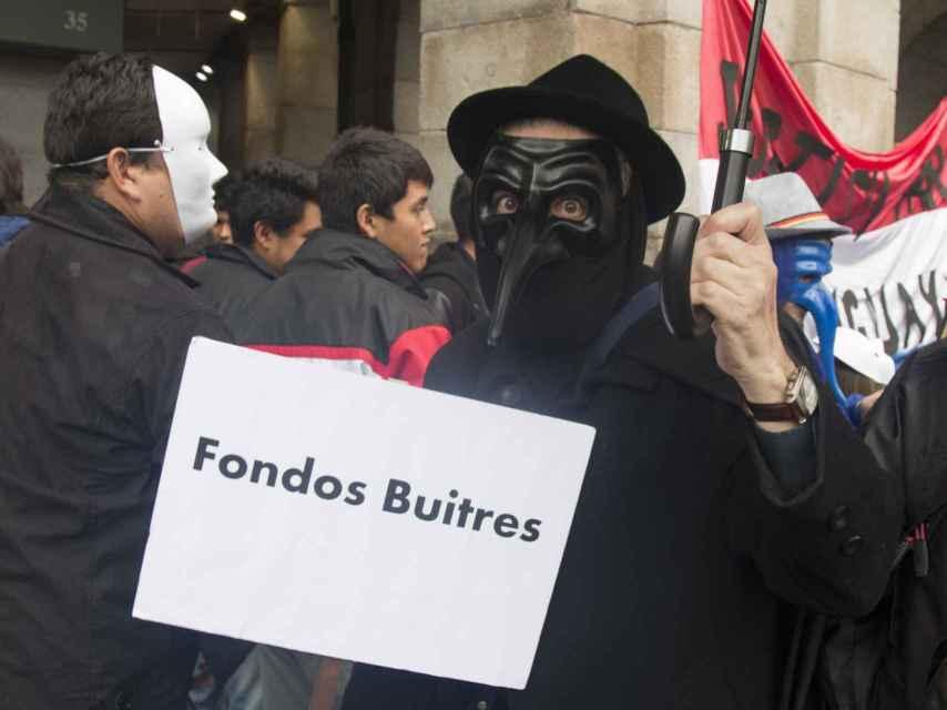 Un hombre porta un cartel contra los fondos buitre durante la manifestación
