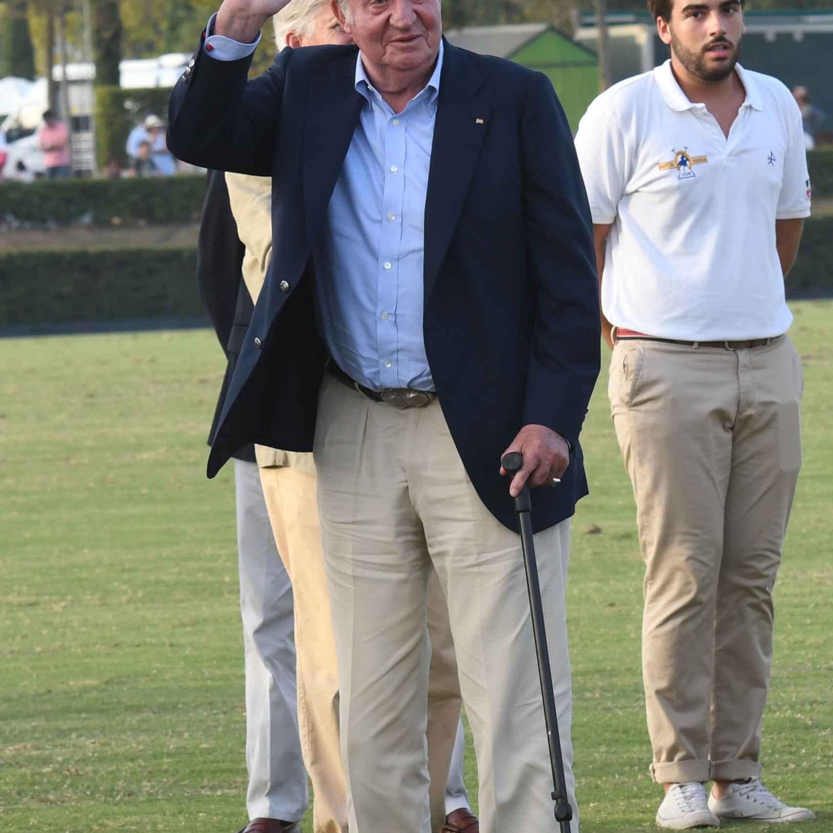 El rey Juan Carlos camina ayudado por un bastón.