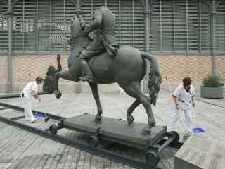 Dos trabajadores instalan la estatua de Franco delante del Born.