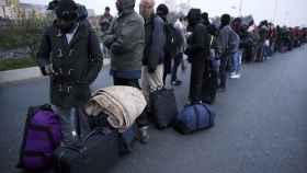 Inmigrantes esperando en 'La Jungla' para ser desalojados.