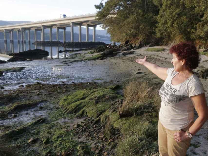 Una mujer señala el lugar donde apareció el teléfono.