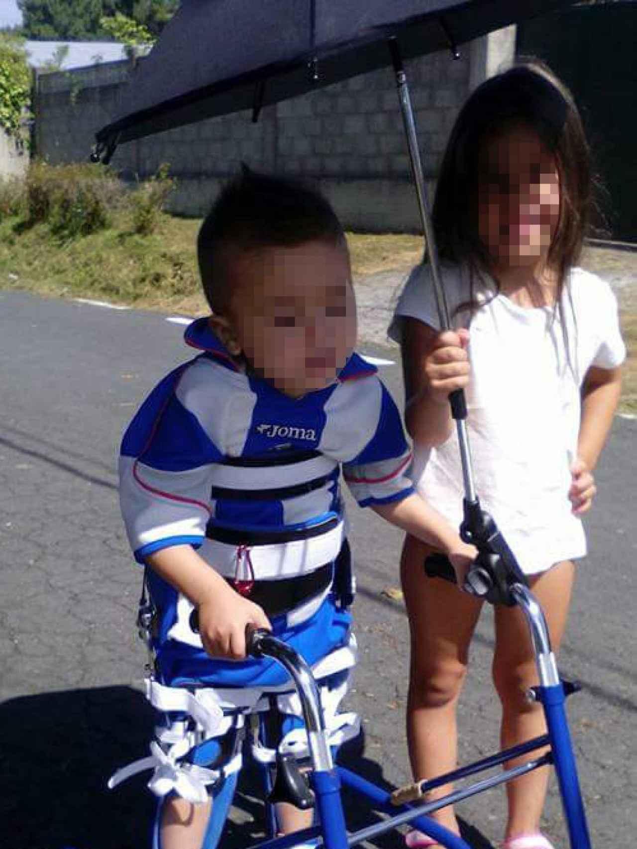 Sara sostiene el paraguas mientras su hermano Marco hace un gran esfuerzo para mantenerse erguido en los reciprocadores.