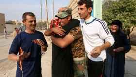 Un combatiente kurdo abraza a su hermana tras arrebatar al EI una localidad al norte de Mosul.