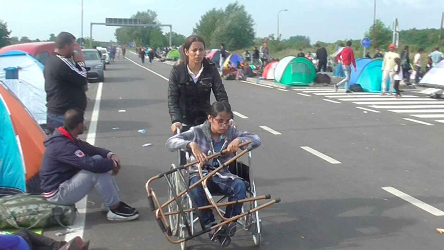 La hermana de Nujeen la ayuda para  avanzar junto a los demás demandantes de asilo.