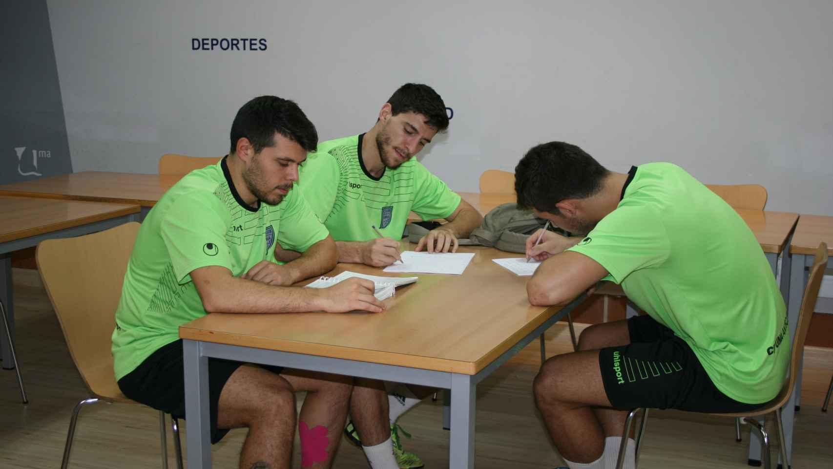 Juanra, Miguel Conde y  Miguel Fernández estudian antes de entrenar.