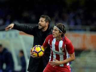 Simeone da instrucciones y Filipe Luis saca la pelota a su lado.