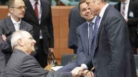 Guindos saluda al ministro alemán Wolfgang Schäuble durante la reunión del Eurogrupo