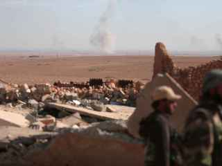 Rebeldes sirios cerca de un edificio bombardeado al norte de Raqa