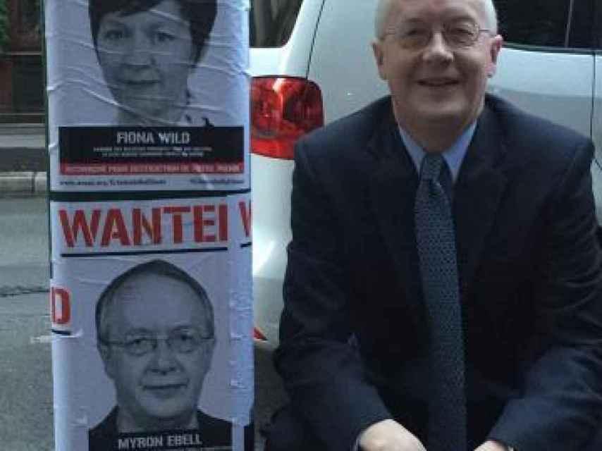 Myron Ebell, junto al cartel que lo tilda de criminal climático.