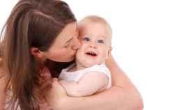 Una mamá besa a su bebé.