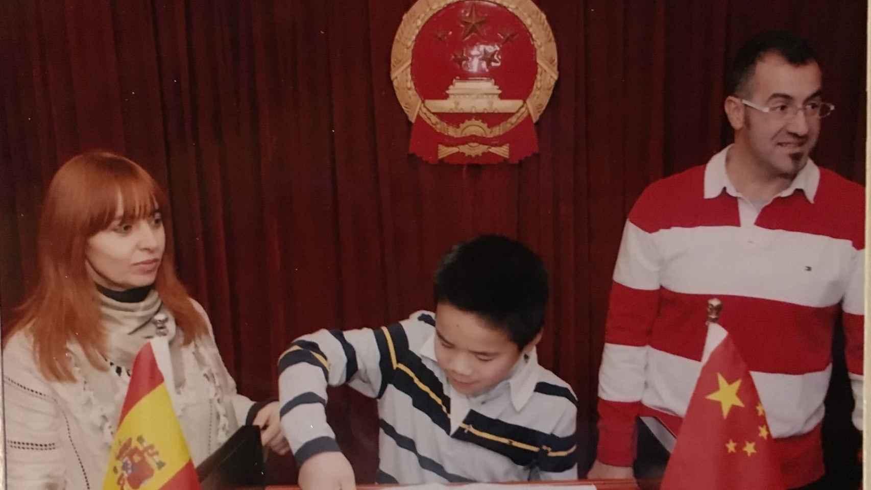 Daniel y sus padres firmando los papeles de adopción.
