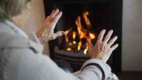 Una anciana se calienta frente a una chimenea.