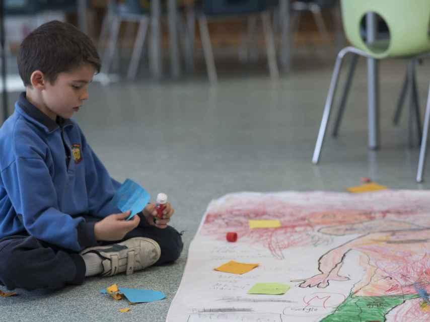 Uno de los alumnos pegando sobre el mural lo que piensa sobre sus compañeras