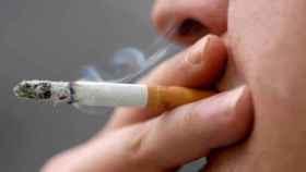 Un hombre se fuma un cigarrillo.