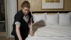 Una camarera de piso arregla una cama en un hotel.