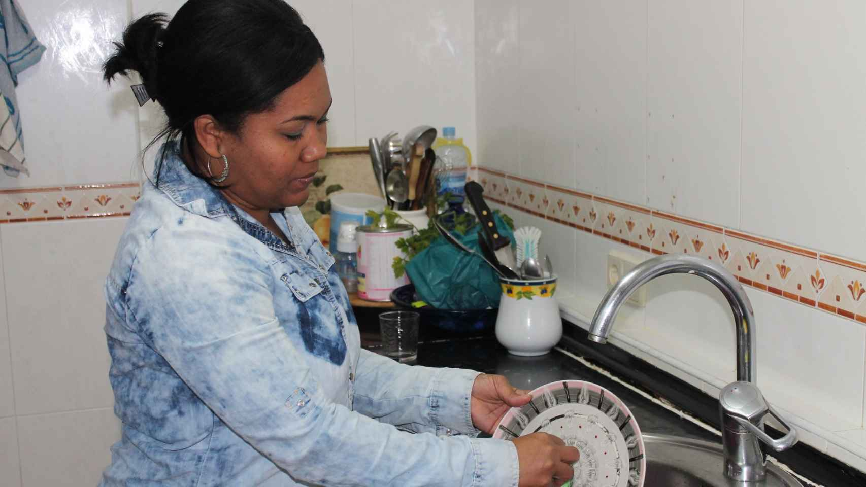 Juliana lava los platos en la cocina del piso que ocupa tras ser desahuciada de su domicilio