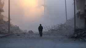 Un hombre se desplaza en su bicicleta tras un ataque sobre un barrio opositor en Alepo el 26 de noviembre.