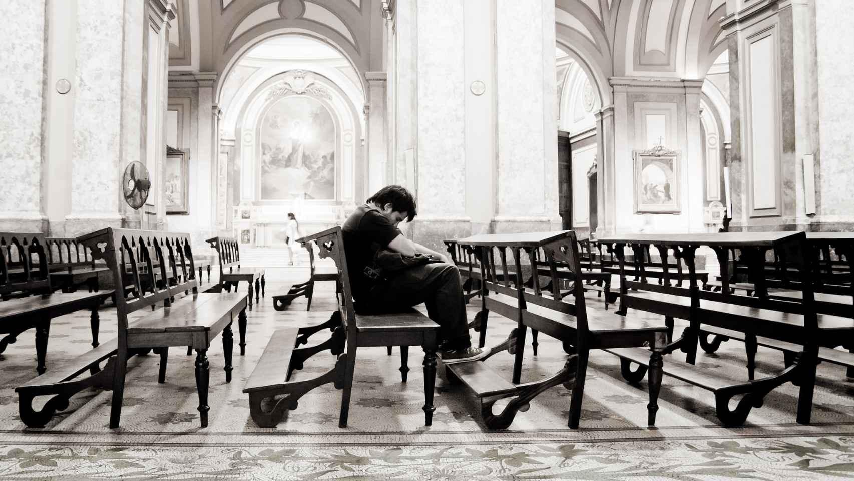 Un hombre reza en soledad.