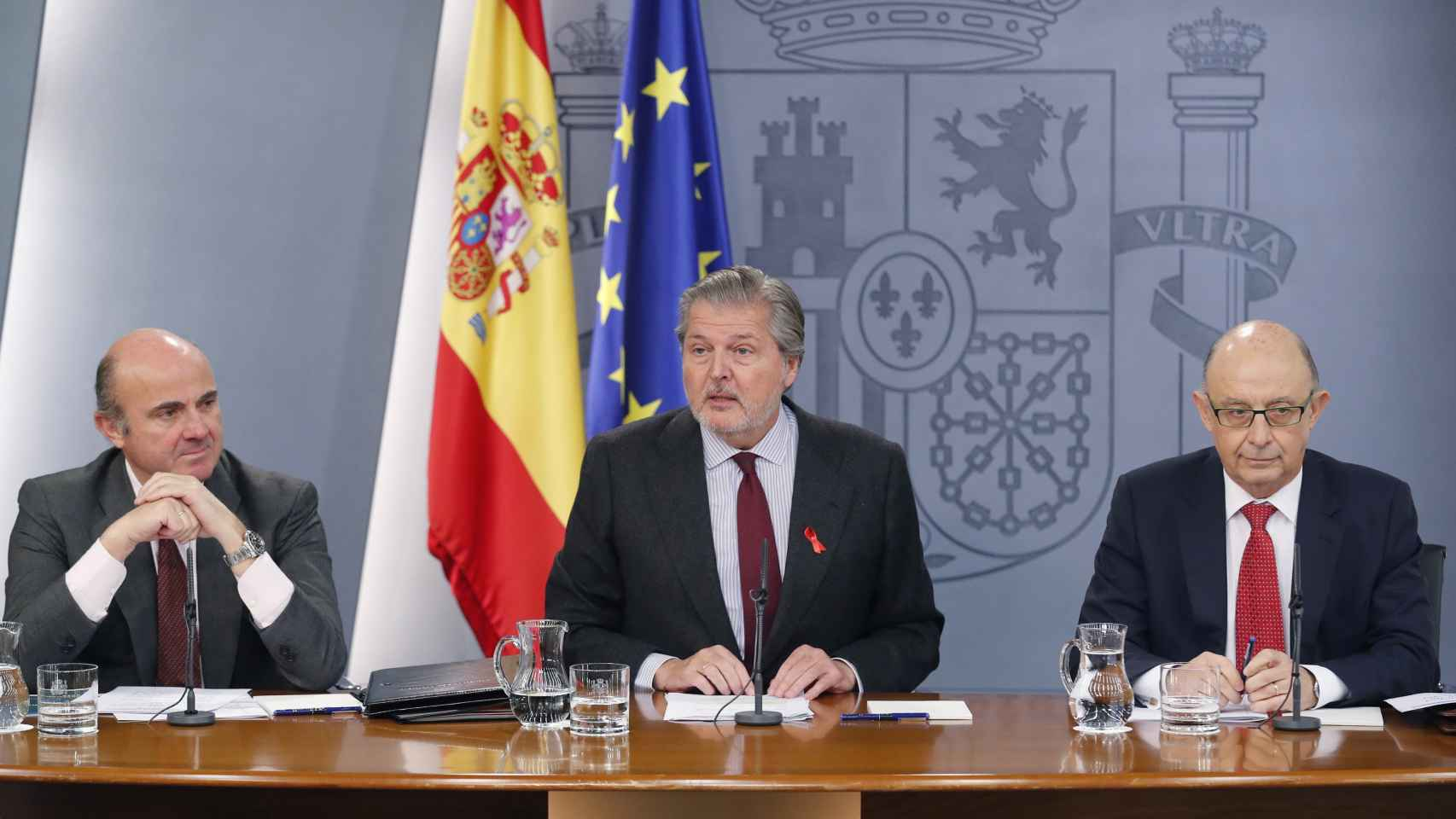 El portavoz del Gobierno, Íñigo Méndez de Vigo (c), junto al ministro de Economía, Industria y Competitividad, Luis de Guindos (i), y el ministro de Hacienda, Cristóbal Montoro (d).