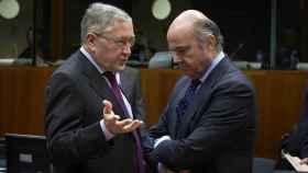 Guindos conversa con el director del Fondo de Rescate de la UE, Klaus Regling, durante el Ecofin