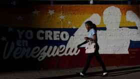 Una mujer camina ante un mural de una calle de Caracas.