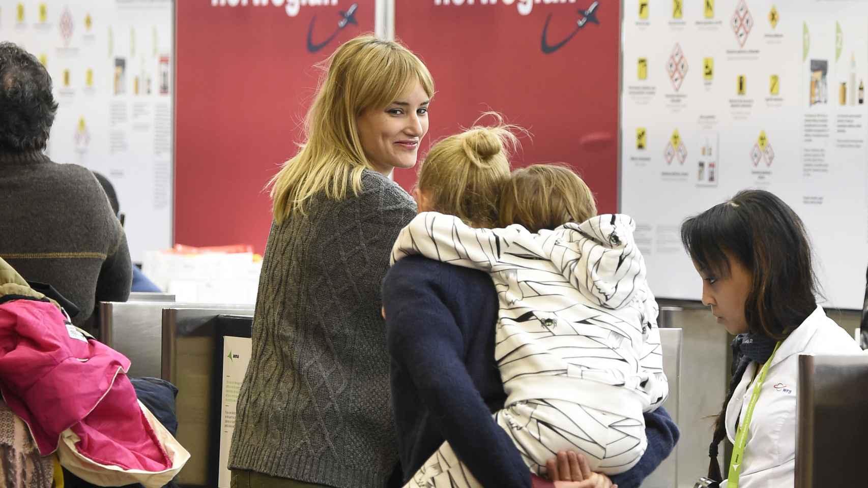 Alba Carrillo sonriente con su madre y su hijo en el aeropuerto de Madrid
