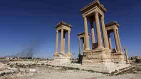 Ruinas de la ciudad histórica de Palmira, con humo al fondo en la ciudad moderna.