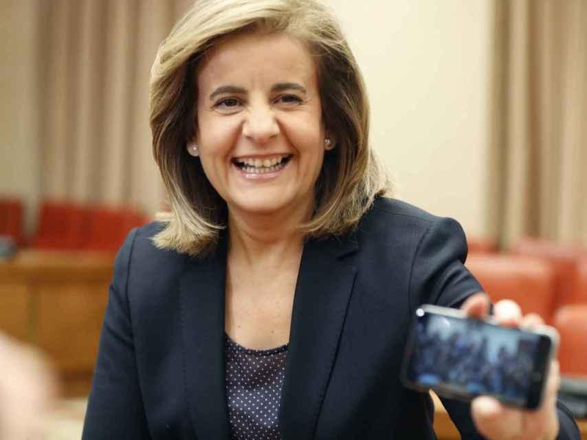 La ministra Fátima Báñez enseña una imagen a los fotógrafos.