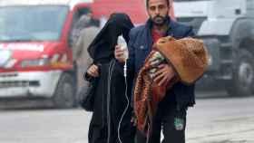 Un hombre lleva a un bebé con un gotero mientras huye más hacia el interior de la zona rebelde de Alepo.