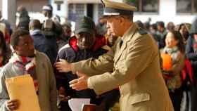 Un policía marroquí habla a un migrante en la cola para regularizarse en Rabat.