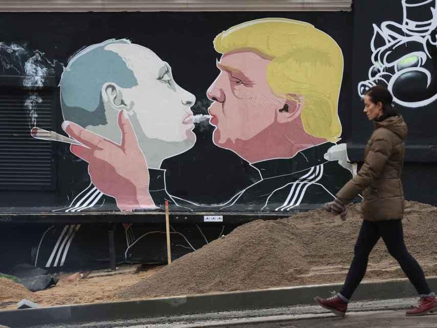 Una mujer recorre un mural en Vilnius, Lituania, que muestra a Trump fumando marihuana en la boca junto a Vladimir Putin.