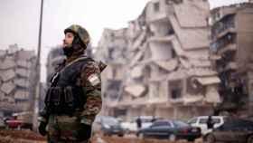 Un soldado de las fuerzas leales a Asad, cerca de edificios dañados en Alepo.