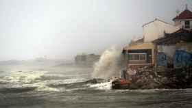 Las olas rompen sobre una casa junto a la playa en Guardamar del Segura (Alicante)